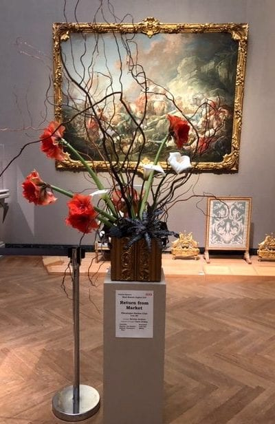 An artistic flower arrangement rests on a pedestal with a painting in the background